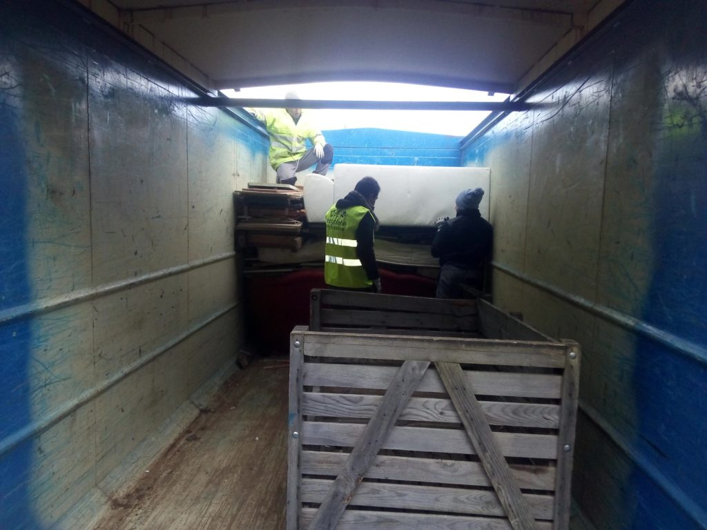 Photo des salariés de la Recyclerie en train de charger une benne de démantèlement